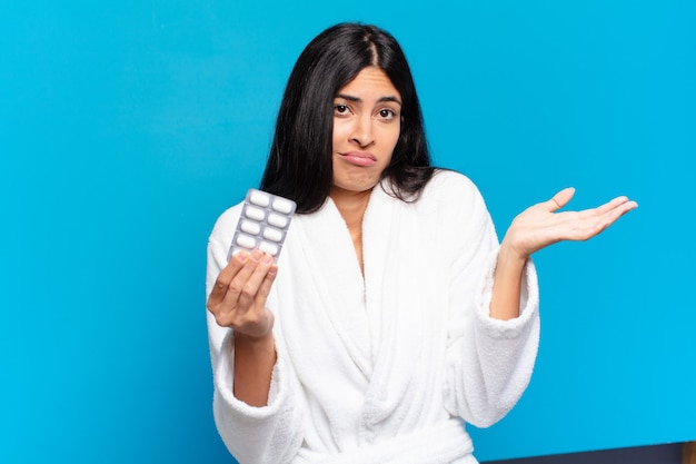 Young pretty hispanic woman with pills tablet. illness concept