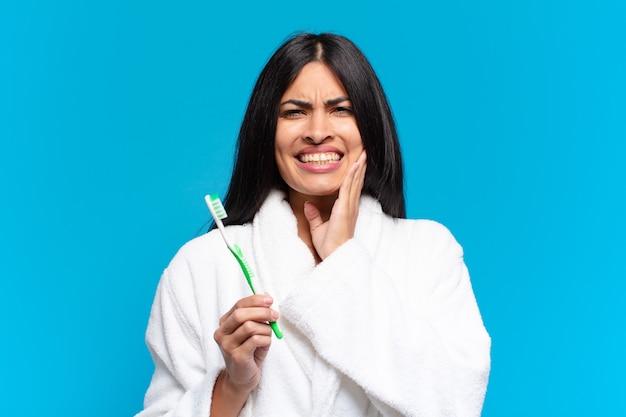 歯痛の若いかなりヒスパニック系の女性