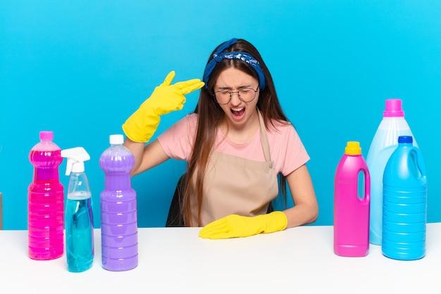 Молодая симпатичная домработница выглядит несчастной и подчеркнутой, жест самоубийства делает знак пистолетом рукой, указывая на голову