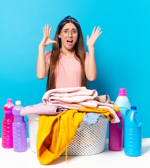 Молодая симпатичная домработница кричит с поднятыми руками, чувствуя ярость, разочарование, стресс и расстройство