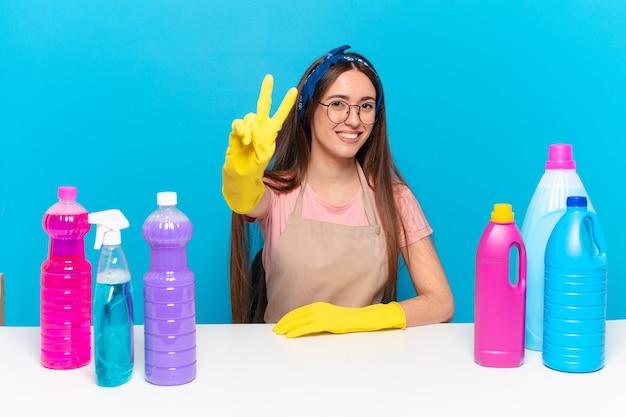 Молодая красивая домработница улыбается и выглядит счастливой, беззаботной и позитивной, жестикулируя победу или мир одной рукой