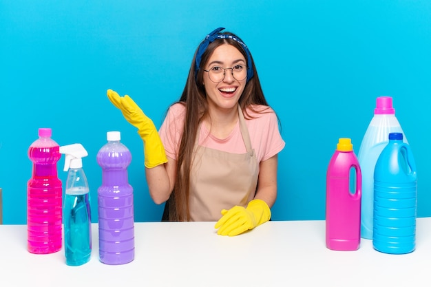 Young pretty housekeeper feeling happy, surprised and cheerful, smiling with positive attitude, realizing a solution or idea