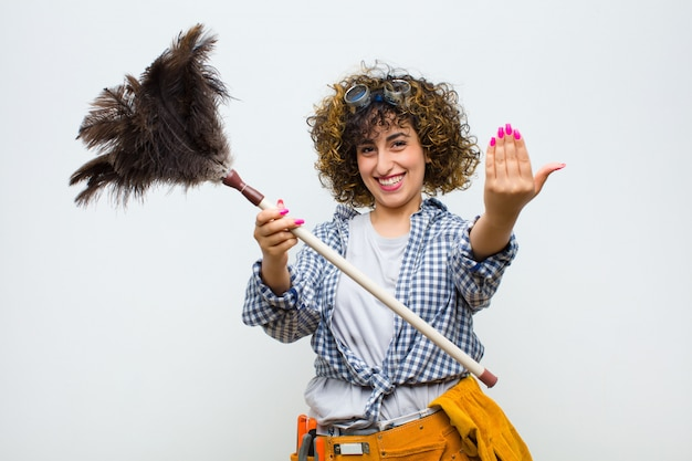 Young pretty housekeeper woman with a duster
