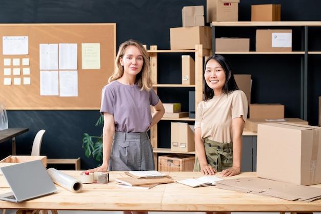 Молодые симпатичные межкультурные работники офиса интернет-магазина, стоящие у деревянного стола во время работы с заказами