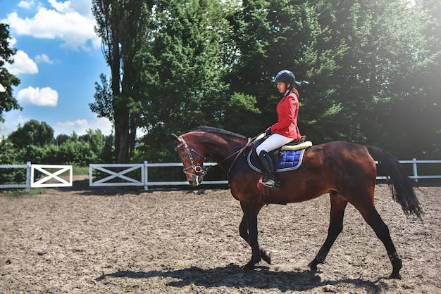 乗るために馬を準備している若いかわいい騎手の女の子。馬が大好きです。馬に乗る少女
