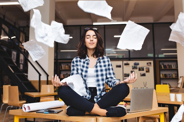 Young pretty joyful brunette woman meditating on table surround work stuff and flying papers. cheerful mood, taking a break, working, studying, relaxation, true emotions.