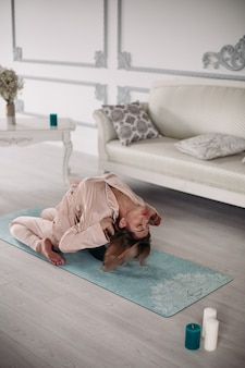 Young pretty lady doing asana at home on yoga mat