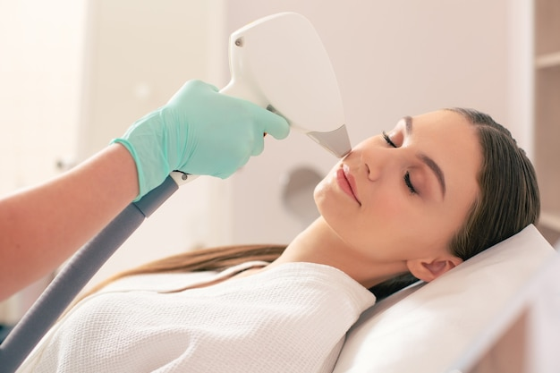 Young pretty lady having her eyes closed while experienced beautician holding a special laser and removing hair on the face of woman