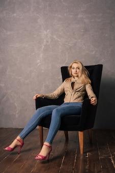 休憩をとっている肘掛け椅子に座っているジーンズと革のジャケットの若いきれいな女性