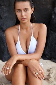 예쁜 아가씨가 절벽의 가장자리에 앉아 바다 또는 바다 수평선을 지켜보고 있습니다.