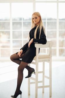 창으로 포즈를 취하는 동안 흰색 의자에 앉아 예쁜 아가씨