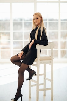 Young pretty lady sitting on white chair while posing with window