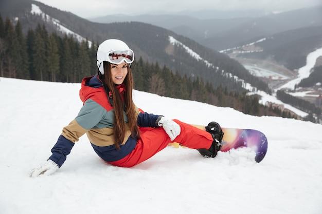 Молодая симпатичная сноубордистка лежит на склонах морозным зимним днем