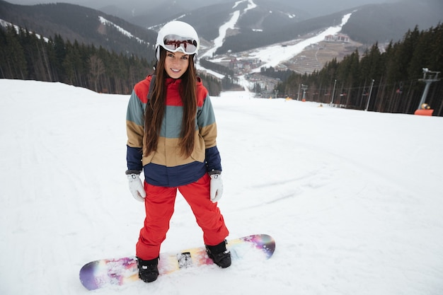 Young pretty lady snowboarder on the slopes frosty winter day