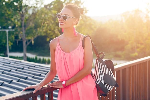 スタイリッシュなサングラスとバックパックを身に着けて、笑顔のピンクのドレスで明るい夏の日にバルコニーに立っている若いきれいな女性