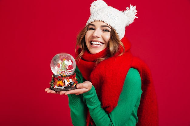 Young pretty lady wearing hat and scarf holding christmas toy