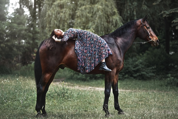 Young pretty latin girl laying on horseback in the forest. love animals concept. love horses