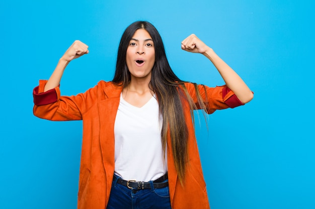 Young pretty latin woman celebrating an unbelievable success like a winner, looking excited and happy saying take that! over wall