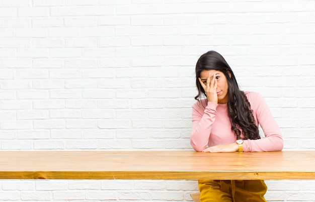 Молодая симпатичная латинская женщина чувствует себя скучно, разочарованно и сонно после утомительного, скучного и утомительного задания, держа лицо рукой, сидя перед столом