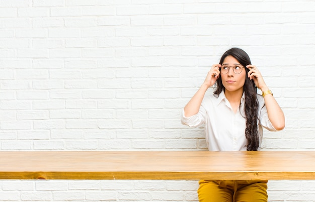 Young  pretty latin woman feeling confused or doubting, concentrating on an idea, thinking hard, looking to copyspace on side sitting in front of a table