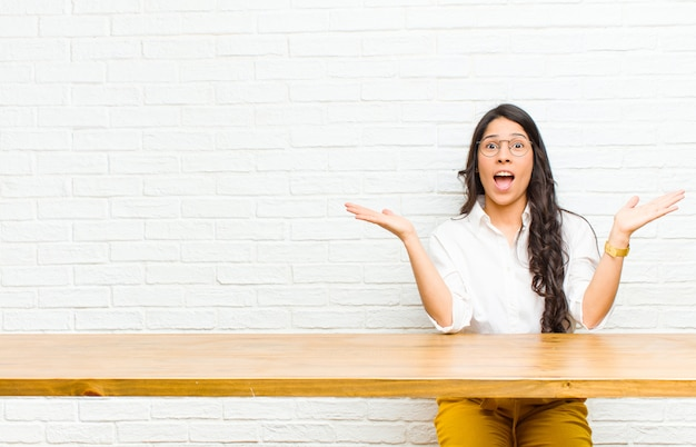 Young  pretty latin woman feeling happy, excited, surprised or shocked, smiling and astonished at something unbelievable sitting in front of a table
