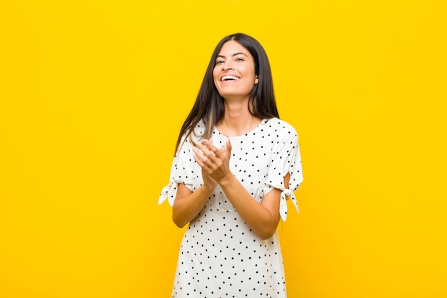 Young pretty latin woman feeling happy and successful, smiling and clapping hands, saying congratulations with an applause against flat wall