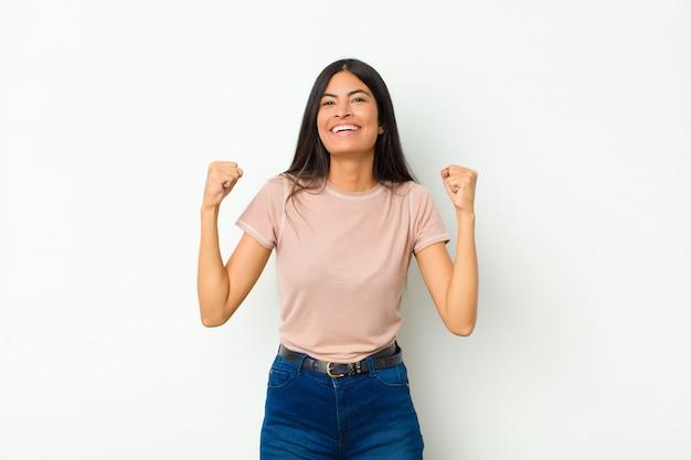 Молодая симпатичная латинская женщина чувствует себя счастливой, удивленной и гордой, кричит и празднует успех с широкой улыбкой у плоской стены
