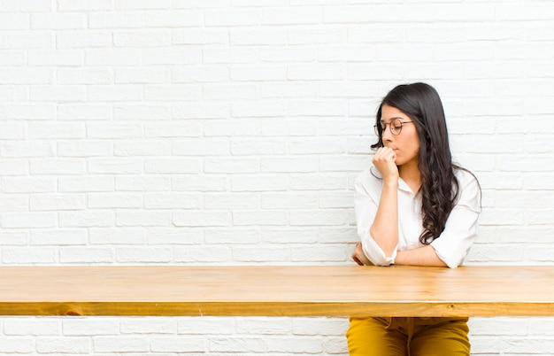 Young  pretty latin woman feeling serious, thoughtful and concerned, staring sideways with hand pressed against chin sitting in front of a table