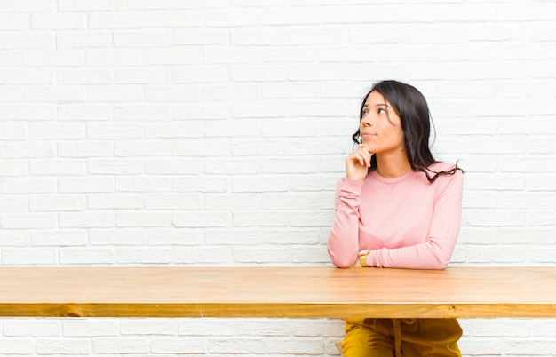 Young  pretty latin woman feeling thoughtful, wondering or imagining ideas, daydreaming and looking up to copyspace sitting in front of a table
