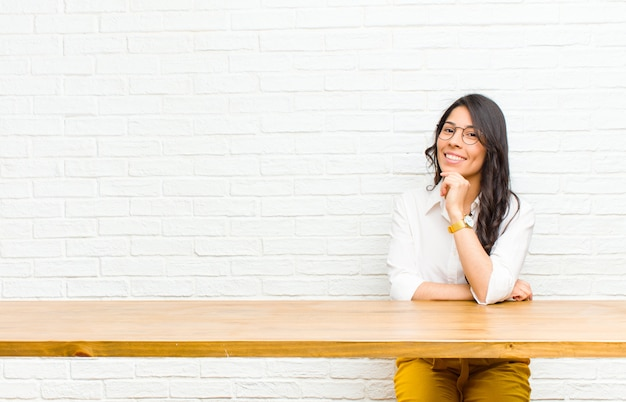 Young  pretty latin woman looking happy and smiling with hand on chin, wondering or asking a question, comparing options sitting in front of a table