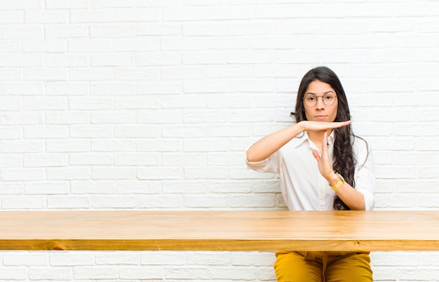 Young  pretty latin woman looking serious, stern, angry and displeased, making time out sign sitting in front of a table