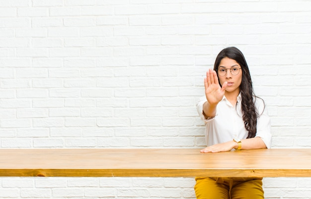 Young  pretty latin woman looking serious, stern, displeased and angry showing open palm making stop gesture sitting in front of a table