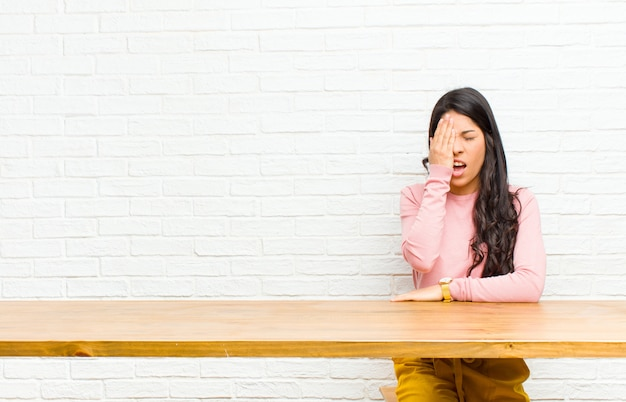 Young  pretty latin woman looking sleepy, bored and yawning, with a headache and one hand covering half the face sitting in front of a table