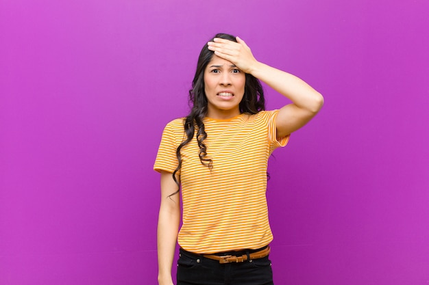 Young pretty latin woman panicking over a forgotten deadline, feeling stressed, having to cover up a mess or mistake against purple wall