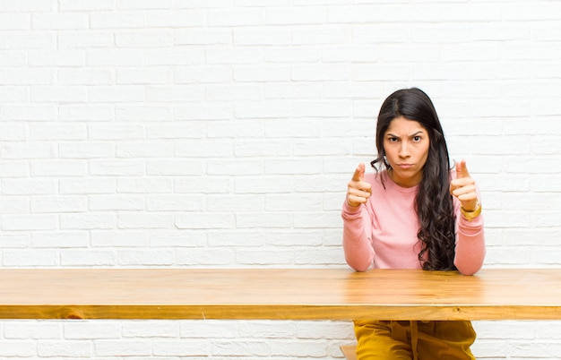 Young  pretty latin woman pointing forward at camera with both fingers and angry expression, telling you to do your duty sitting in front of a table