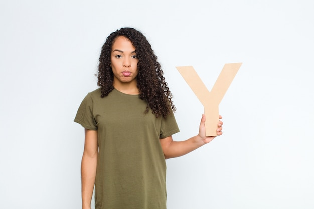 Young pretty latin woman sad, depressed, unhappy, holding the letter y of the alphabet to form a word or a sentence