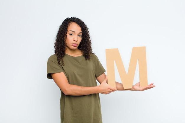悲しい、落ち込んで、不幸な若いかなりラテン女性、単語または文を形成するアルファベットのmの文字を保持しています。