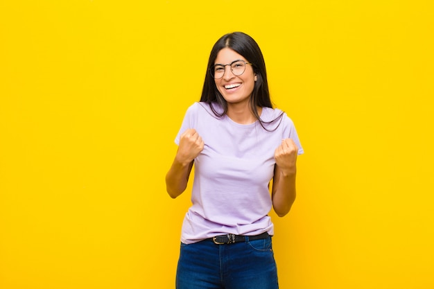 Молодая симпатичная латинская женщина триумфально кричит, смеется и чувствует себя счастливой и взволнованной, празднуя успех у плоской стены