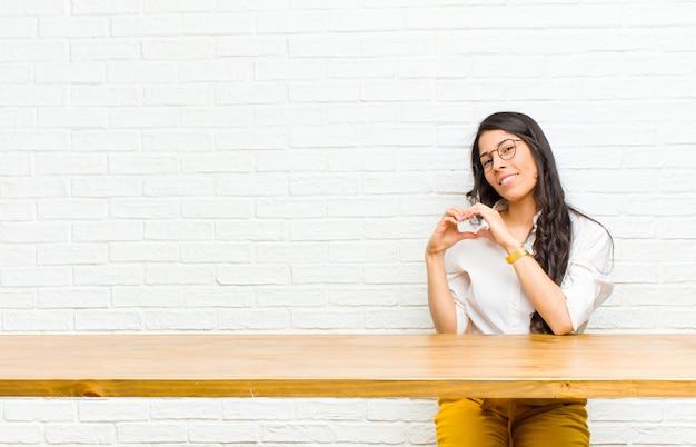 젊은 예쁜 라틴 여자 웃 고 행복, 귀여운, 로맨틱 하 고 사랑에 두 손으로 테이블 앞에 앉아 심장 모양 만들기