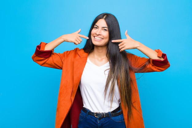 Young pretty latin woman smiling confidently pointing to own broad smile, positive, relaxed, satisfied attitude against flat wall