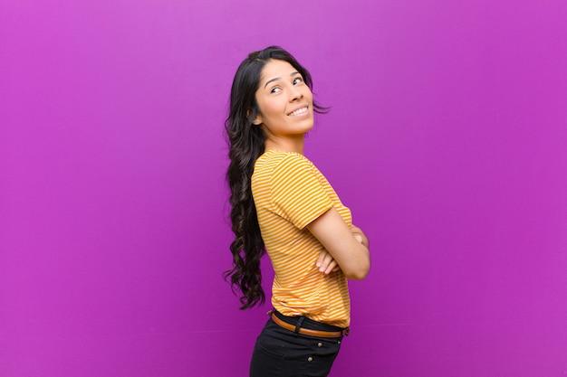 젊은 꽤 라틴 여자 기쁘게 웃고, 행복 느낌, 만족과 편안한, 교차 팔과 보라색 벽에 측면을 찾고