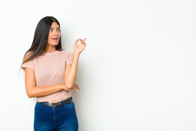 若い可愛いラテン女性の幸せそうに笑って横を向いて、不思議に思って、または平らな壁に対してアイデアを持っている