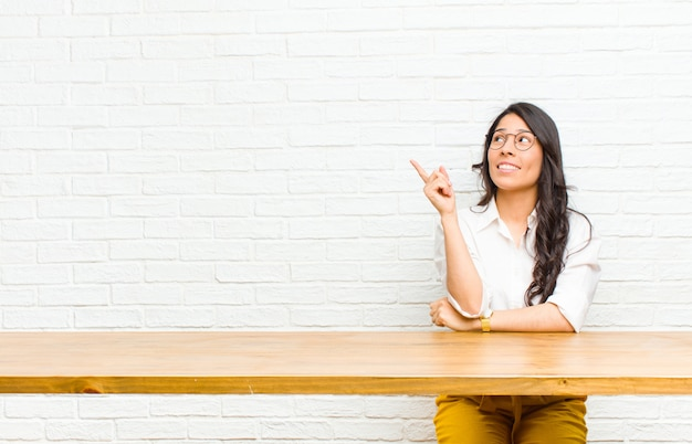 Young  pretty latin woman smiling happily and looking sideways, wondering, thinking or having an idea sitting in front of a table