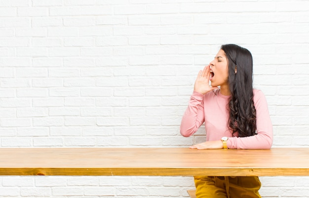 Young  pretty latin woman yelling loudly and angrily to copyspace on the side, with hand next to mouth sitting in front of a table