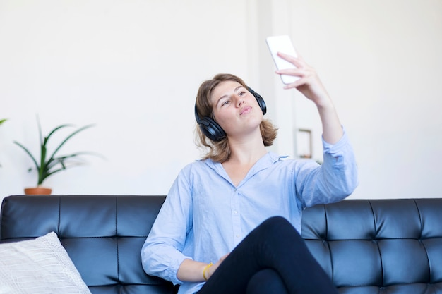 Young pretty long hair woman sitting on a sofa making selfie on her phone