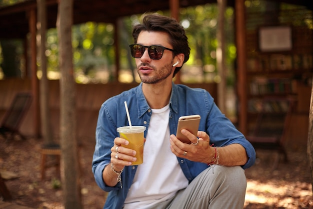 Young pretty male with beard having lunck break out of office, posing over city garden with ice tea in hand, going to make call with his mobile phone