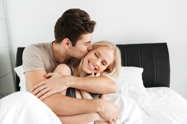 Молодой симпатичный мужчина целует и обнимает свою счастливую жену