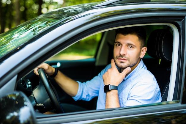 車に座っている若いきれいな男