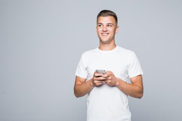 Giovane uomo grazioso in una maglietta bianca isolata sul telefono bianco della stretta nelle sue mani