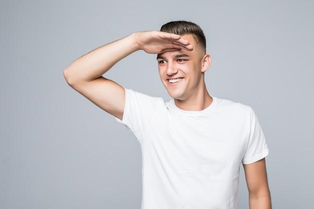 Il giovane uomo grazioso in una maglietta bianca isolata su bianco attende con impazienza